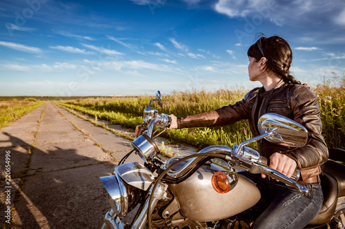 Fototapete Biker girl sitting on motorcycle