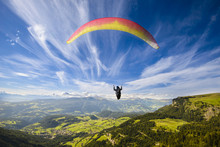 Fototapete - Paraglider flying over mountains