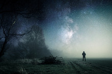 Fototapete - A lone hooded figure standing on a path on a spooky misty night, with a cold blue edit.