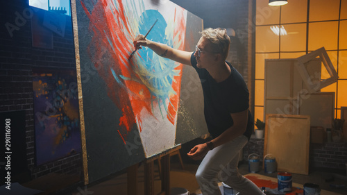 Fototapete Talented Artist Working on Abstract Painting, Uses Paint Brush To Create Daringly Emotional Modern Picture. Dark Creative Studio Large Canvas Stands on Easel Illuminated.